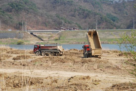 ▲  4대강 사업으로 강에서 퍼올린 준설토를 인근 농경지에 쌓았다가, 골재 반출이 끝나고 남은 슬러지를 강변에 퍼붓고 있다. ⓒ 김종술