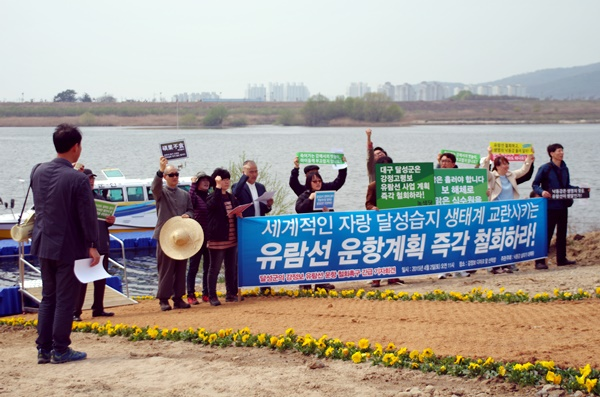 """""""달성군은 유람선 운항계획 즉각 중단하라!"""" 낙동강 살리기 대책위 활동가들과 시민들이 강정보 디아크 아래서 기자회견을 열고 있다.ⓒ대구환경운동연합"""