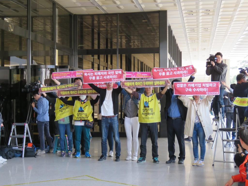 신전대표를 향해 피해자와 환경단체 회원들이 '내 아이와 내 아내가 하늘에서 보고 있다', '억울하게 죽어간 우리 아이를 살려내라' 펼침막을 펼쳐 보이고 있다.
