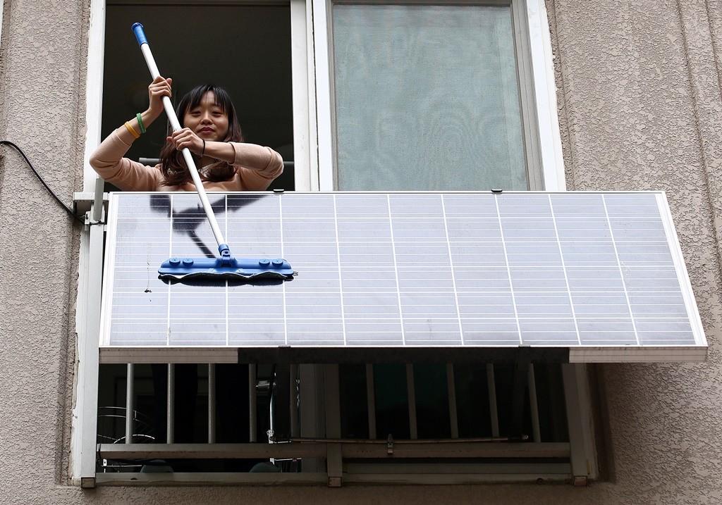 한 시민이 아파트 베란다에 설치된 미니 태양광 발전소를 청소하고 있다. 사진제공=이성수/함께사는길