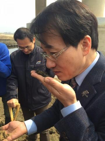 사문진교에서 퍼낸 흙의 냄새를 맡는 이원욱 의원(국토위)