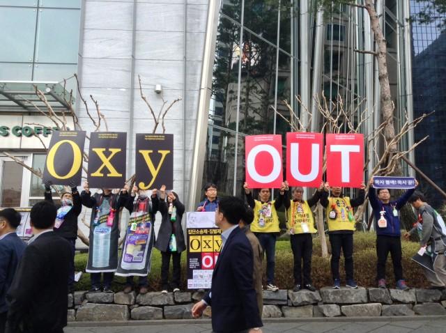 옥시 본사 앞에서 '옥시 아웃(OxyOUT)'이라고 쓰인 손팻말을 들고 캠페인을 진행하고 있다ⓒ가습기넷
