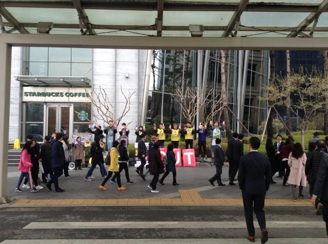 옥시 본사 앞에서 '옥시 아웃(OxyOUT)'이라고 쓰인 손팻말을 들고 캠페인을 진행하고 있다. 많은 시민들이 관심 있게 지켜보고 있다 ⓒ가습기넷