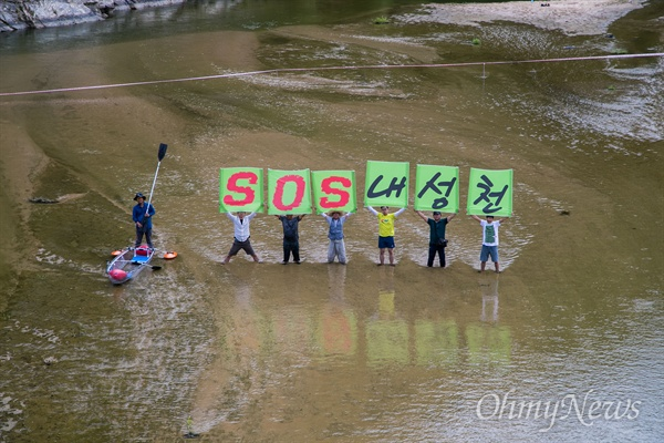 ▲ 환경운동연합, 10만인클럽, 불교환경연대, 대한하천학회 회원들이 경북 예천 내성천 일대에서 강 보존을 위해 'SOS내성천'이 적힌 피켓을 들고 강 위에 서 있다. ⓒ 이희훈