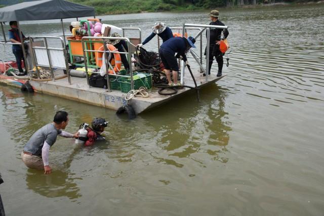 물속의 잠긴 것들을 빼내기 위해 열심히 작업중이다. ⓒ 대구환경연합 정수근