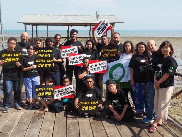 파푸아뉴기니에서 회의 중인 지구의 벗 아태지역 단체 활동가들이 '신고리 5, 6호기 건설중단' 자국어 피켓을 들고 집회에 참여하고 있다. ⓒ환경운동연합