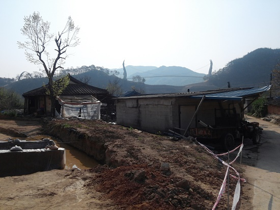 수몰되기 전 금강마을의 애잔한 풍경 너머로 댐에 물이 차오를 때 대비해 건설중인 현수교가 보인다. ⓒ 카리나 슈마허