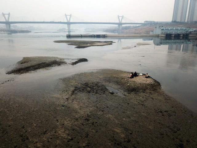 세종보 상류 드러난 모래톱 웅덩이에 갇힌 물고기를 넣어주던 작업자들이 쉬고 있다.ⓒ김종술