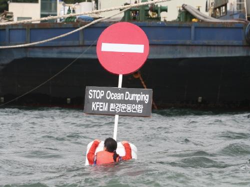 ▲  감천항 바다에 뛰어들어 수중시위를 하는 바다위원회 여성 활동가